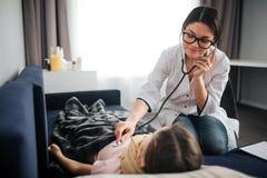 Luistert de jonge vrouwelijke arts van Nice aan de ademhaling van het kind door stethoscoop Zij glimlacht en bekijkt meisje De ar stock fotografie