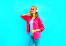 Luistert de manier glimlachende vrouw aan muziek in draadloze hoofdtelefoons in roze denimjasje op blauw royalty-vrije stock afbeelding