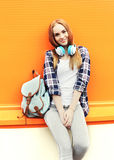 Luistert het manier mooie glimlachende meisje met hoofdtelefoons aan muziek Stock Foto