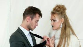 Lujuria, mirada apasionada, individuo en el traje negro que intenta besar a la muchacha rubia con los labios oscuros que llevan e metrajes