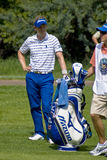 Luke Donald and Caddy. Luke Donald takes a moments rest leaning on his bag supported by his caddy Stock Image