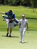 Luke Donald and Caddy. Luke Donald strolling green, putter in hand. His caddy following directly behind with the bag of clubs Stock Photo