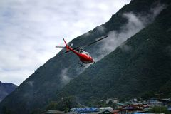 LUKLA, NEPAL - 20 SEPTEMBER 2017: Red Helicopter Leaving Tenzing–Hillary Airport stock photography