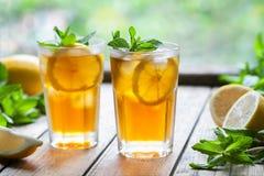 Lukrowa herbata z cytryna plasterkami i mennica na drewnianym stole z widokiem drzew i tarasu Zamyka w górę lato napoju Zdjęcia Royalty Free