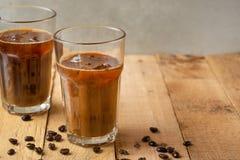 Lukrowa kawa w przejrzystych szk?ach z lodem i s?oma, na drewnianym tle, od?wie?aj?cy nap?j, od?wie?enie, lato nastr?j, z obrazy stock