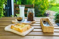Lukrowego sześcianu kawowy latte z dojnym i strzałem kawa espresso i grzanki polewa z zgęszczonym mlekiem i cutlery na drewnianym Obrazy Royalty Free
