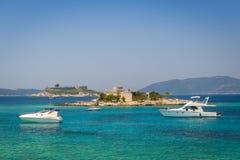Luksusów motorowi jachty przy kotwicą blisko starego fortecy na małej wyspie obraz stock