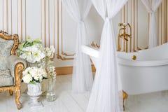 Luksusowa łazienka w lekkich kolorach z złotymi mebli szczegółami, baldachimem i Elegancki klasyczny wnętrze fotografia stock