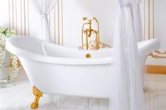 Luksusowa łazienka w lekkich kolorach z złotymi mebli szczegółami, baldachimem i Elegancki klasyczny wnętrze zdjęcia stock