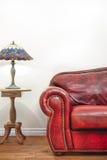 Luksusowa Czerwona Rzemienna leżanka przed pustą ścianą Obraz Stock