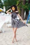 Luksusowa podróży kobieta w czarny i biały beachwear odprowadzeniu bierze przespacerowanie na piaska lata plaży Dziewczyna turyst fotografia royalty free