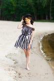 Luksusowa podróży kobieta w czarny i biały beachwear odprowadzeniu bierze przespacerowanie na piaska lata plaży Dziewczyna turyst fotografia stock