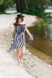 Luksusowa podróży kobieta w czarny i biały beachwear odprowadzeniu bierze przespacerowanie na piaska lata plaży Dziewczyna turyst zdjęcie stock