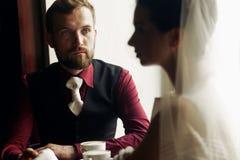 Luksusowe ślub pary mienia ręki i pić kawa w kawiarni Zdjęcia Royalty Free