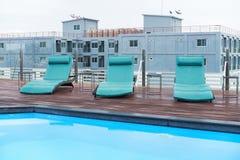 Luksusowi sunbeds na drewnianym podłogowym pobliskim pływackim basenie Obrazy Royalty Free