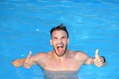 Luksusowy basen - z podnieceniem Seksowny facet w błękitne wody na plaży Potężna mięśniowa męska postać na błękit plaży zdjęcie stock