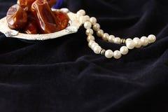 Luksusowy bogactwa srebra puchar z datami i perła koralikami na ciemnej jedwabniczej tkaninie obraz stock