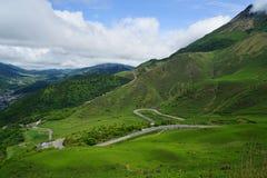 Luksusowy greenery kształtuje teren panoramę góra Yufu, dróg linie i grodzki widok z chmurnym niebem od daleko, obrazy stock