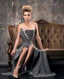 Luksusowy kobiety obsiadanie na rocznik kanapie Formalny piękny i włosy siwiejemy suknię zdjęcie royalty free