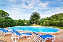 Luksusowy pływacki basen z słońc loungers. Dla relaksu. Zdjęcie Stock
