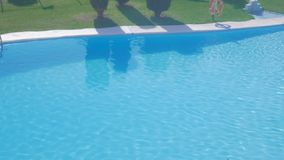 Luksusowy plenerowy basen z słońc odbiciami na pogodnym letnim dniu zbiory wideo