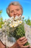 Lukta blommor för hög kvinna. Royaltyfri Foto