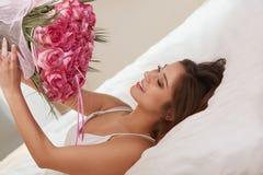 Lukta för kvinna blommor, medan ligga på hennes säng Royaltyfria Bilder