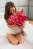 Lukta för kvinna blommor, medan ligga på hennes säng Royaltyfri Bild
