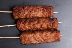 Lula kebab στο ξύλινο σκοτεινό ψήσιμο οβελιδίων Στοκ Φωτογραφίες