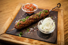 Lula kebab with tomato salsa. Lula kebab. Prepared from meat of black angus. Served with tomato salsa Stock Images