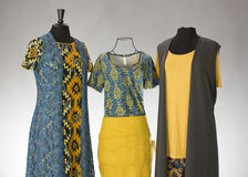 LuLaRoe Clothing Collection. A gold and teal themed collection of LuLaRoe brand clothing is displayed on three mannequins.  The layered outfits are made of Stock Images