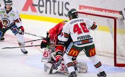 Lulea Sverige - mars 18, 2015 Christoffer Persson (indier för #46 Frolunda) dubbelcheckar Lennart Petrell (hockey för #32 Lulea)  Arkivfoton
