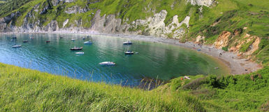 Lulworth cove with boats in blue water Royalty Free Stock Image