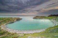 Lulworth liten vik på den Jurassic kusten av Dorset på solnedgången royaltyfria bilder