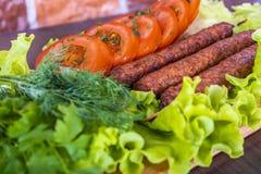 Lulya-kebab 在棍子的烤肉串,肉末 传统白种人盘 在一个切板上,用蔬菜沙拉,番茄酱,香料 库存图片