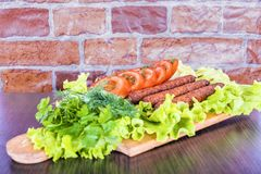 Lulya-kebab 在棍子的烤肉串,肉末 传统白种人盘 在一个切板上,用蔬菜沙拉,番茄酱,香料 库存照片