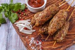 Lulya-kebab 在棍子的烤肉串,肉末 传统白种人盘 用蔬菜沙拉,番茄酱,香料 库存图片