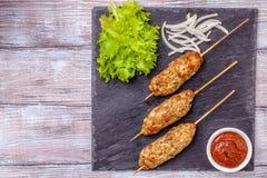 Lulya-kebab Kebab на ручке, семенить мясо Shish Традиционное кавказское блюдо С зеленым салатом, кетчуп, специи Стоковые Фотографии RF
