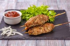 Lulya-kebab Kebab en un palillo, carne picadita Plato caucásico tradicional Con la ensalada verde, salsa de tomate, especias Foto de archivo