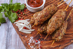 Lulya-kebab. Shish kebab on a stick, minced meat. Traditional Caucasian dish. With green salad, ketchup, spices. Lulya-kebab. Shish kebab on a stick, minced stock image
