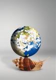 Lumaca con il globo sulle coperture su fondo grigio Fotografia Stock