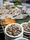 Lumaca di Babilonia del primo piano nel piatto della carta e pesci blured, calamari, frutti di mare immagini stock