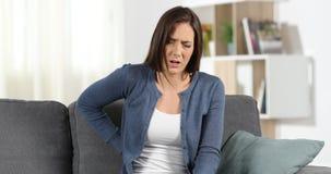 Lumbago sufridor de la mujer en un sofá almacen de video