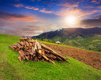 Lumber on agriculture field in mountains at sunset. Lumber and wooden planks on agriculture field with arable near village in mountains at sunset stock images