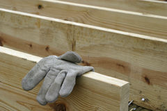 Lumber and Glove. Worker's glove draped over a beam of wood in a sub-floor on a construction site Stock Photos