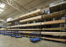 Lumber interior warehouse. Commercial  indoor lumberyard with carts in front of lumber Stock Photo