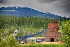 Lumber mill in a small town. Working lumber mill surrounded by forests and mountains. British Columbia, Canada Stock Image