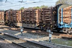 Lumber on the move. A freight train travels slowly south on the UK west coast main line near Warrington, laden with lumber, destination unknown Stock Images