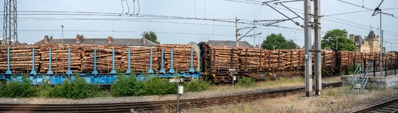 Lumber train fully laden. A freight train fully laden with lumber/logs passes slowly by, heading south on the UK west coast mainline, destination unknown Stock Images