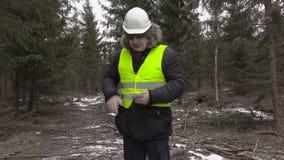 Lumberjack с банкнотами евро и умный телефон в лесе видеоматериал